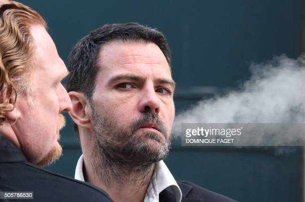TOPSHOT French convicted rogue trader Jerome Kerviel flanked by his lawyer Benoit Pruvost smokes outside the courthouse of Versailles on January 20...