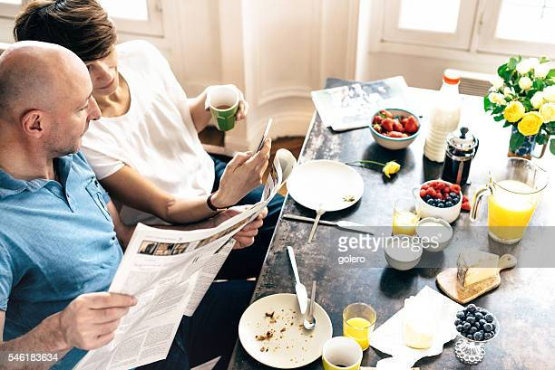 french couple with mobile and newspaper at breakfast table