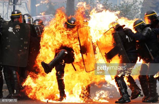 TOPSHOT French CRS antiriot police officers are engulfed in flames as they face protesters during a march for the annual May Day workers' rally in...