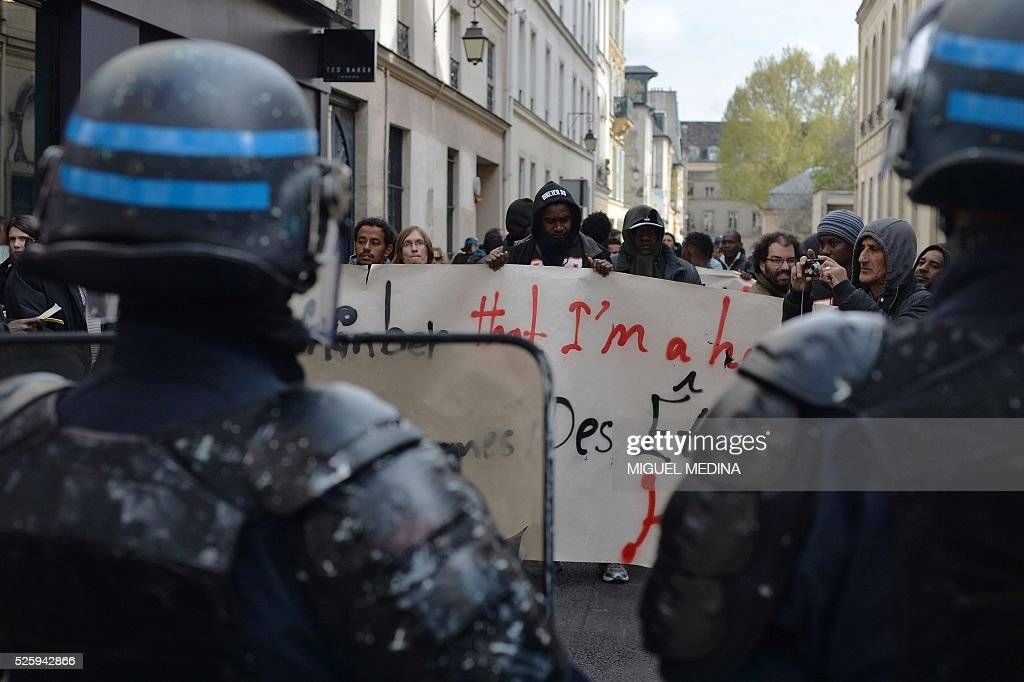 French CRS anti-riot police stand facing migrants who have occupied a high school in Paris' nineteenth district during a demonstration to call for better living conditions in Paris on April 29, 2016. The Regional Council has appealed to the administrative court which will consider on April 29 its request for the immediate evacuation of the migrants from the Jean Jaures high school in the nineteenth arrondissement of Paris. The high school, currently under construction, was occupied by some 150 migrants on the night of April 28. / AFP / MIGUEL