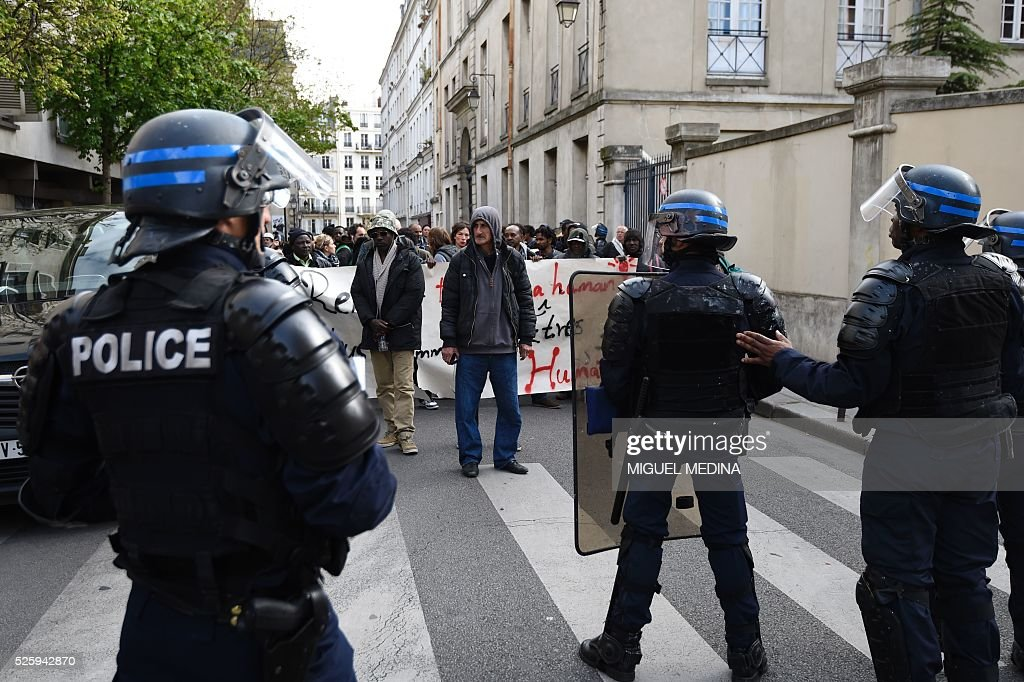 French CRS anti-riot police stand facing protesters and migrants who have occupied a high school in Paris' nineteenth district during a demonstration to call for better living conditions in Paris on April 29, 2016. The Regional Council has appealed to the administrative court which will consider on April 29 its request for the immediate evacuation of the migrants from the Jean Jaures high school in the nineteenth arrondissement of Paris. The high school, currently under construction, was occupied by some 150 migrants on the night of April 28. / AFP / MIGUEL