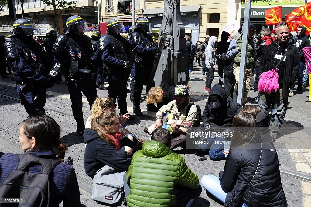 French CRS anti-riot police stand guard as people sit on the floor as they demonstrate in the streets of Marseille during the traditional May Day rally on May 1, 2016. / AFP / Franck PENNANT