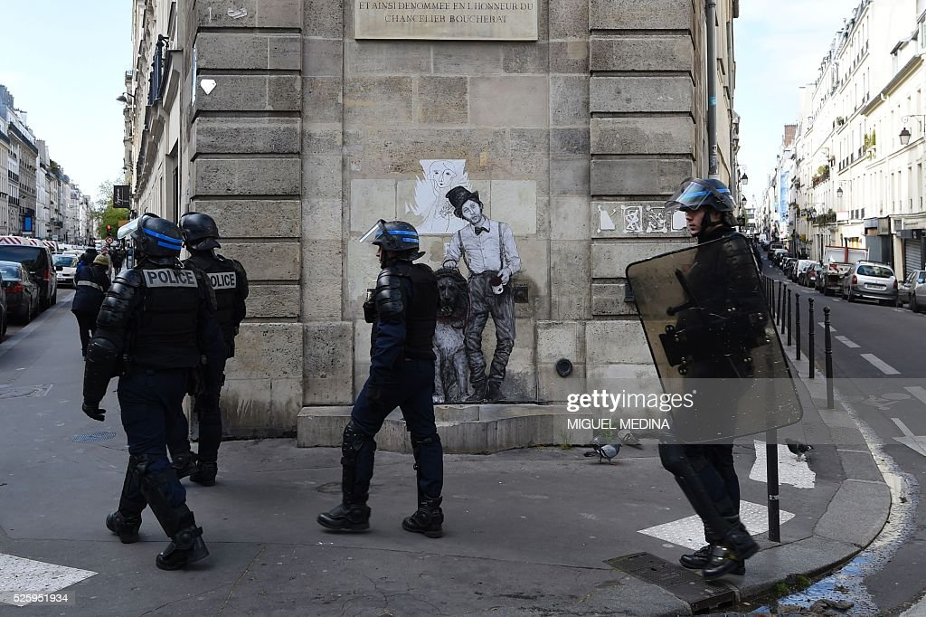 French CRS anti-riot police walk behind protesters, including migrants who have occupied a high school in Paris' nineteenth district, during a demonstration to call for better living conditions in Paris on April 29, 2016. The Regional Council has appealed to the administrative court which will consider on April 29 its request for the immediate evacuation of the migrants from the Jean Jaures high school in the nineteenth arrondissement of Paris. The high school, currently under construction, was occupied by some 150 migrants on the night of April 28. / AFP / MIGUEL