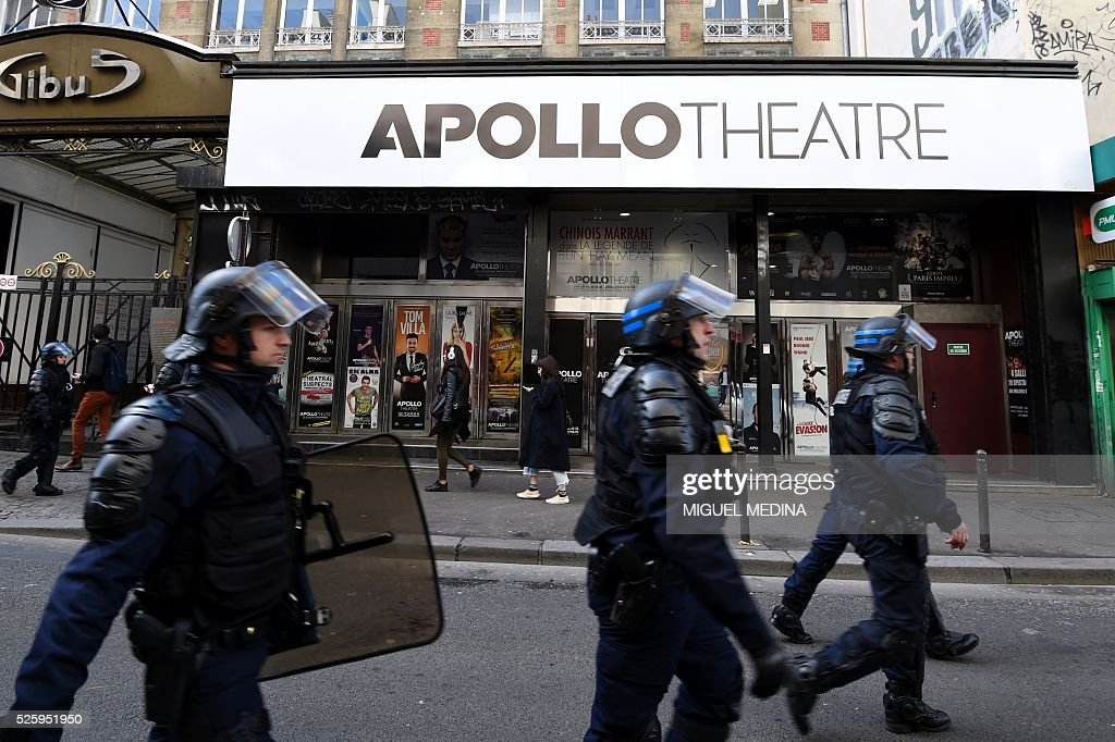 French CRS anti-riot police walk past the Apollo Theatre as they flank protesters, including migrants who have occupied a high school in Paris' nineteenth district, during a demonstration to call for better living conditions in Paris on April 29, 2016. The Regional Council has appealed to the administrative court which will consider on April 29 its request for the immediate evacuation of the migrants from the Jean Jaures high school in the nineteenth arrondissement of Paris. The high school, currently under construction, was occupied by some 150 migrants on the night of April 28. / AFP / MIGUEL