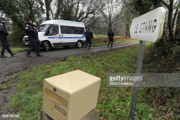 French CRS police officers stand as they investigate near the house of Lydie Troadec sister of Pascal Troadec who went missing with his wife and two...
