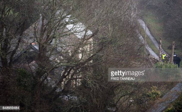 French CRS police officers stand near the house of Lydie Troadec sister of Pascal Troadec who went missing with his wife and two children and his...