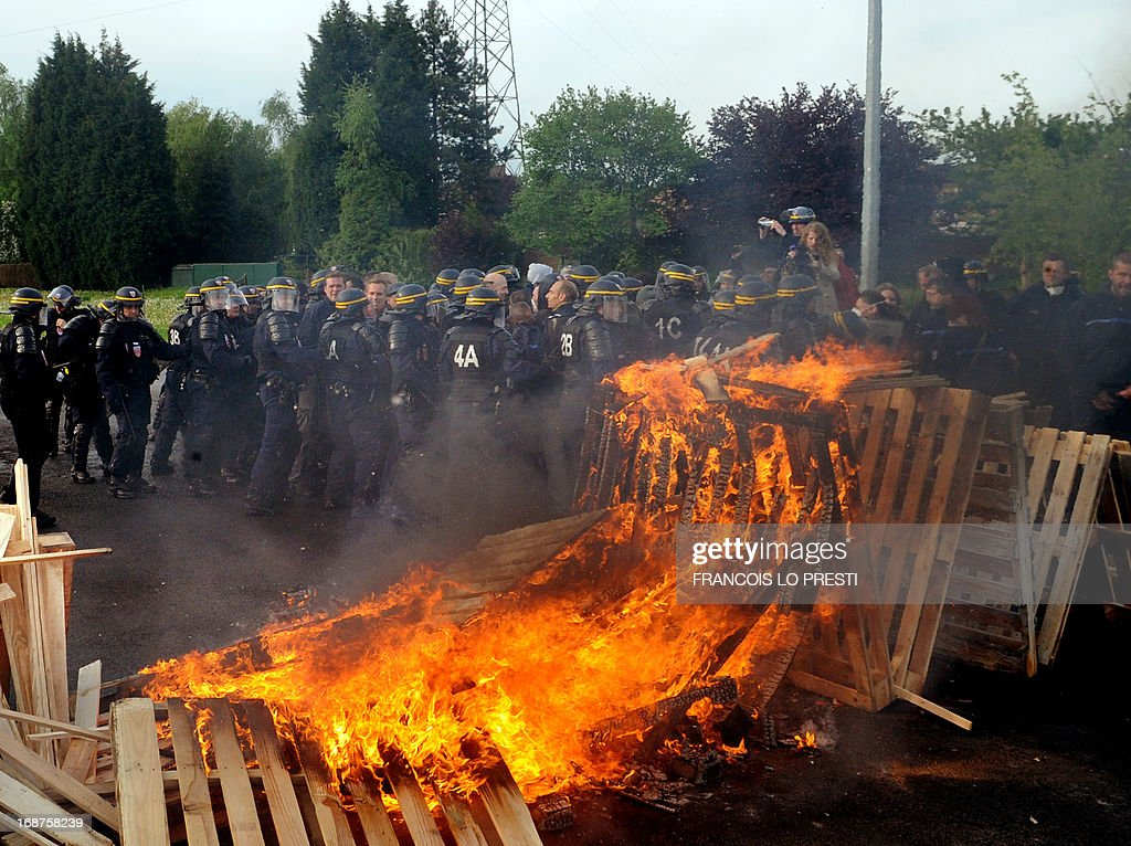 French CRS riot police clash with prison guards at the Sequedin remand centre, as wooden pallets were set on fire, in Sequedin, northern France, on May 15, 2013. Prison guards blocked the access to the remand centre for three hours this morning to protest against a lack of security measures at the jail, one month after Redoine Faid's dramatic escape. PRESTI