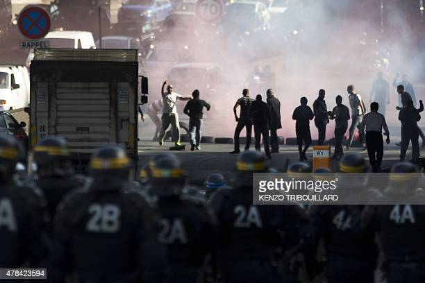 French CRS riot police face demonstrators as striking taxi drivers block the Boulevard Peripherique near Porte Maillot in Paris on June 25 2015...