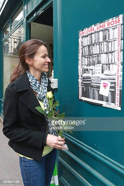 French Culture Minister Aurelie Fileppetti handing a rose reads a poster at the entrance of a Paris bookshop on April 27 which celebrates the 15th...