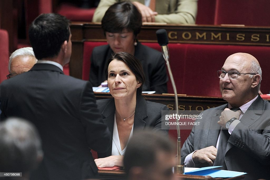 French Culture Minister Aurelie Filippetti (C) and French Finance Minister Michel Sapin (R) attend a session of questions to the government at the French National Assembly on June 17, 2014, in Paris.