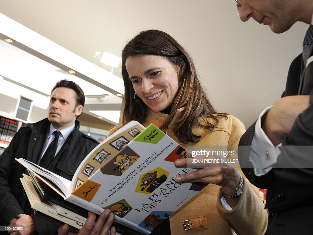 French Culture Minister Aurelie Filippetti looks at a comic during the opening of the 40th International Comic book festival of Angouleme on January 31, 2013. AFP PHOTO JEAN PIERRE MULLER