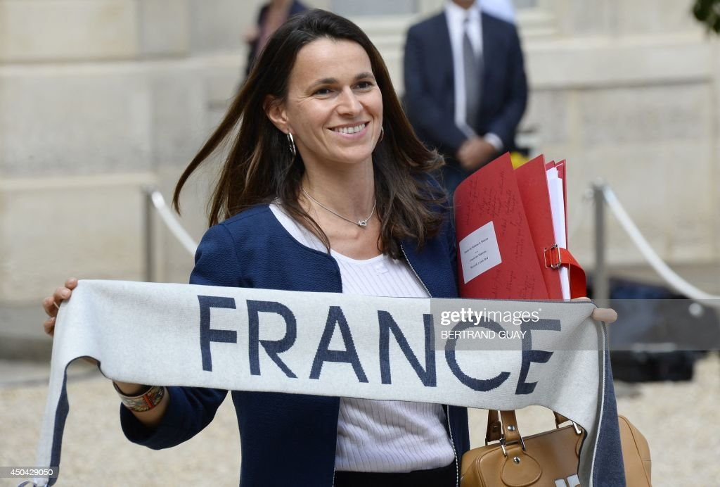 French Culture minister Aurelie Filippetti shows a scarf to support the French national football team as she leaves the Elysee presidential palace in Paris, after the weekly cabinet meeting on June 11, 2014. The players arrived in Brazil last Monday, three days ahead of the FIFA World Cup 2014.