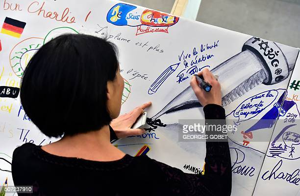 French Culture minister Fleur Pellerin signs on the 'drawings wall' during an exhibition dedicated to Charlie Hebdo on January 28 2016 in Angouleme...