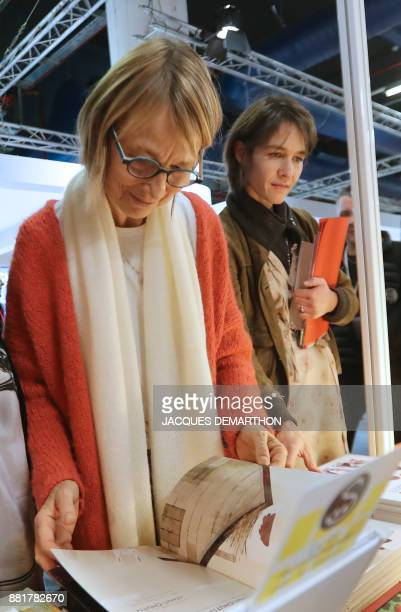 French Culture Minister Francoise Nyssen looks at a book as she attends the inauguration of the Montreuil Youth Book Fair at Montreuil on the...