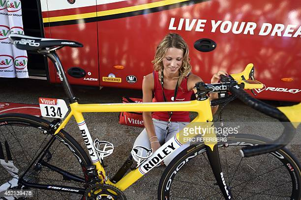 French cyclist Marion Rousse and girlfriend of France's Tony Gallopin wearing the overall leader's yellow jersey looks at the yellow bike of Tony...