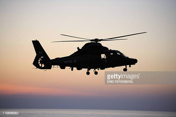 A French Dauphin helicopter flies over the French aircraft carrier Charles De Gaulle on March 24 on her way for a mission to Libya President Nicolas...