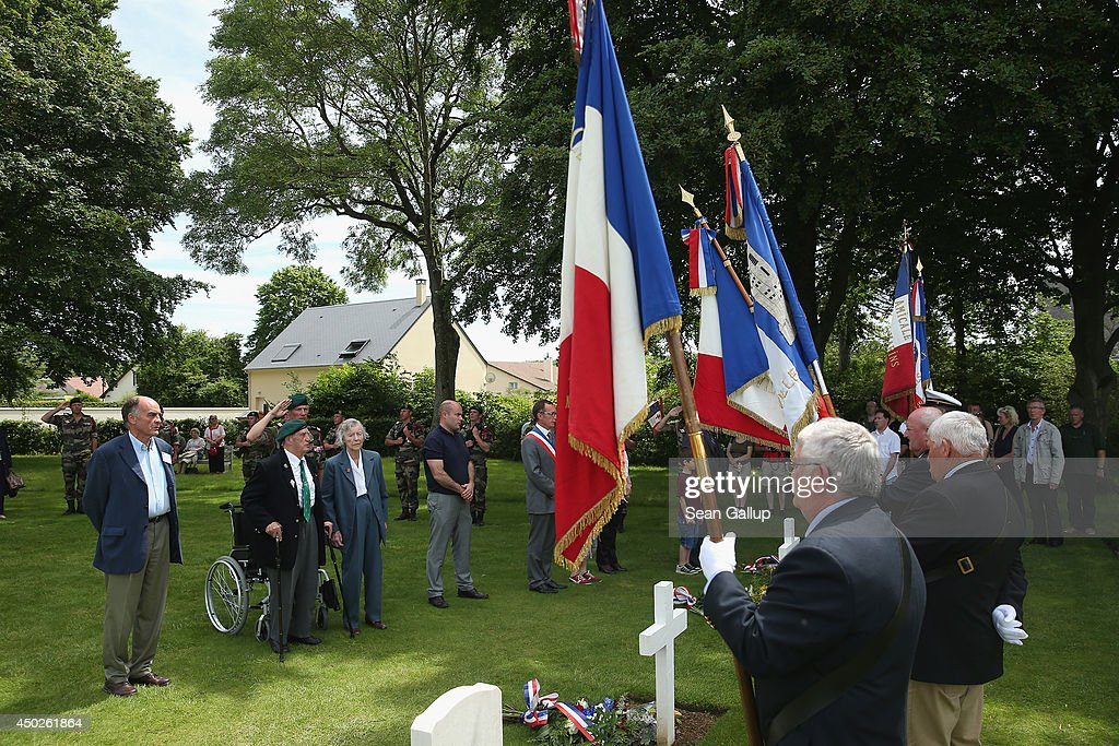 French D-Day veteran Leon Gautier (2nd from L), who served in the Troop One unit of free French commandos under Lieutenant Phlippe Kiefer and who landed at Sword Beach during the World War II D-day invasion, and family members of other veterans attend a wreath-laying ceremony at the military cemetery on June 7, 2014 in Ranville, France. Friday the 6th of June is the 70th anniversary of the D-Day landings that saw 156,000 troops from the Allied countries, including the United Kingdom and the United States, join forces to launch an audacious attack on the beaches of Normandy, these assaults are credited with the eventual defeat of Nazi Germany. A series of events commemorating the 70th anniversary are planned for the week with many heads of state travelling to the famous beaches to pay their respects to those who lost their lives.