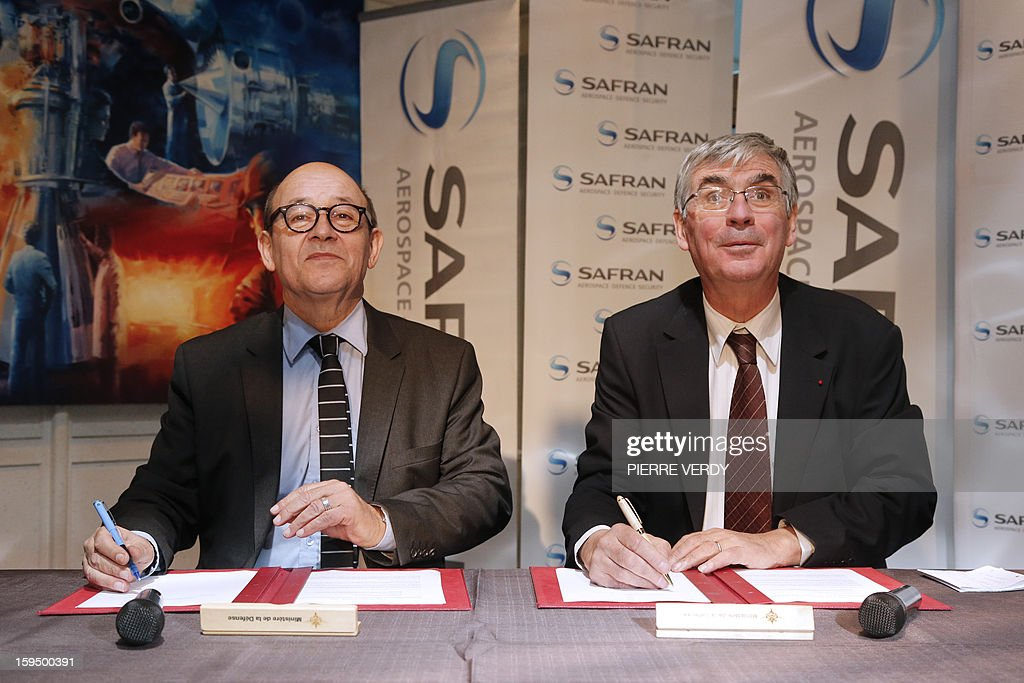French Defence minister Jean-Yves le Drian (L) and CEO of French aerospace and defence group Safran, Jean-Paul Herteman sign agreements to promote the development of SME subcontractors of the group Safran, on January 14, 2012 at the Safran / Snecma plant in Gennevilliers, near Paris.
