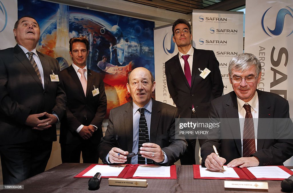 French Defence minister Jean-Yves le Drian (C) and CEO of French aerospace and defence group Safran, Jean-Paul Herteman (R) sign agreements to promote the development of SME subcontractors of the group Safran next to Jean-Claude Lepage (L), chairman of 'Meca Dev', Thomas Corbel (2ndL), chairman of the 'LPF group' and Alain-Jory Barthe (2ndR), chairman of 'Manoir Aerospace Business', on on January 14, 2012 at the Safran / Snecma plant in Gennevilliers, near Paris.