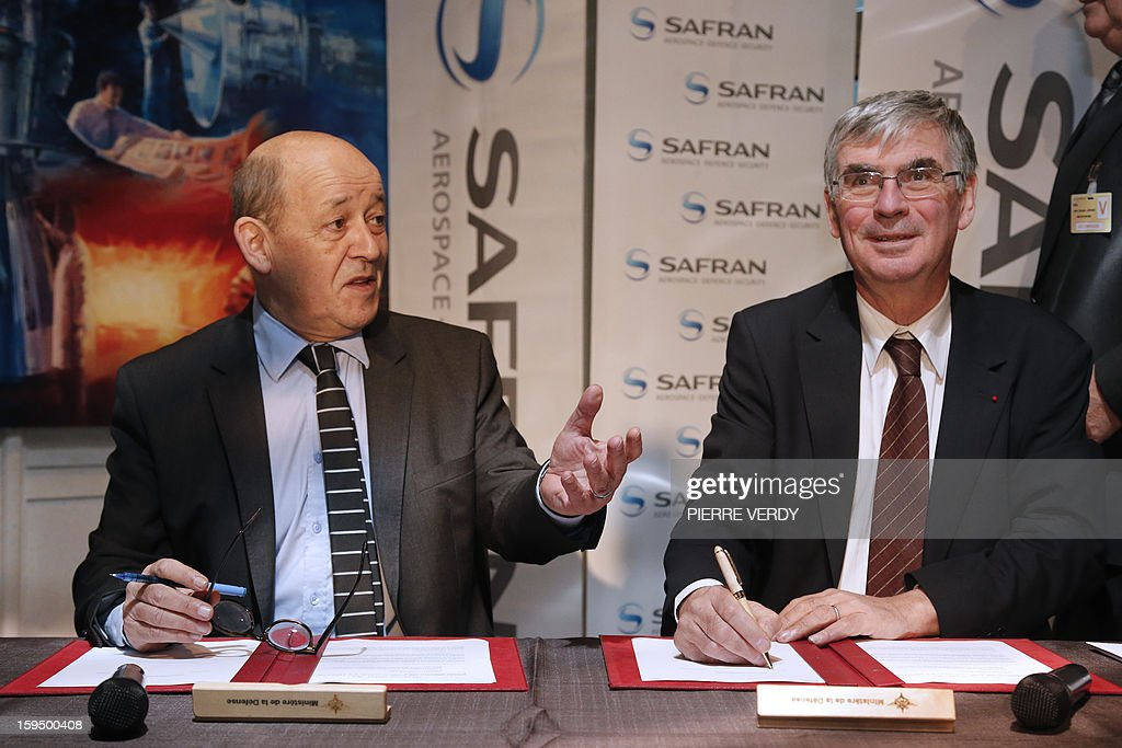 French Defence minister Jean-Yves le Drian (L) and CEO of French aerospace and defence group Safran, Jean-Paul Herteman (R) sign agreements to promote the development of SME subcontractors of the group Safran on January 14, 2012 at the Safran / Snecma plant in Gennevilliers, near Paris.