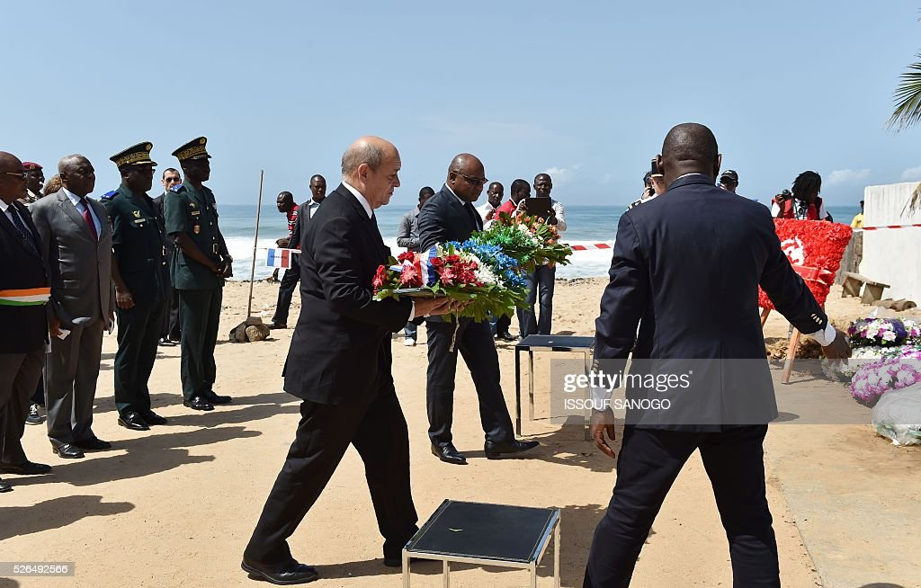 French Defence Minister Jean-Yves Le Drian (C) and the representative of Ivory Coast's defence minister, Jean Paul Malan, prepare to lay wreaths in homage to the victims of a jihadist attack on the beach of the Hotel l'Etoile du Sud in Grand Bassam on April 30, 2016. France will increase the number of its troops in Ivory Coast, Defence Minister Jean-Yves Le Drian said on a trip to the African nation which hosts a regional base for French forces. / AFP / ISSOUF