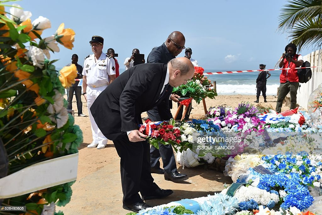 French Defence Minister Jean-Yves Le Drian (C) and the representative of Ivory Coast's defence minister, Jean Paul Malan, lay wreaths in homage to the victims of a jihadist attack on the beach of the Hotel l'Etoile du Sud in Grand Bassam on April 30, 2016. France will increase the number of its troops in Ivory Coast, Defence Minister Jean-Yves Le Drian said on a trip to the African nation which hosts a regional base for French forces. / AFP / ISSOUF