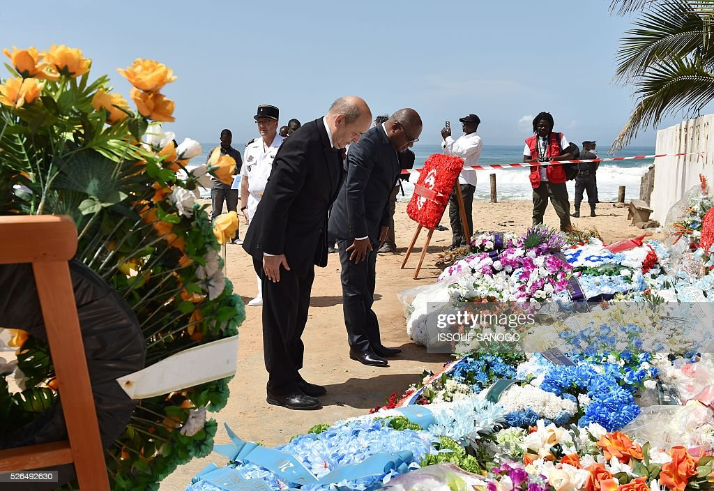 French Defence Minister Jean-Yves Le Drian (C) and the representative of Ivory Coast's defence minister, Jean Paul Malan, bow their heads after laying wreaths in homage to the victims of a jihadist attack on the beach of the Hotel l'Etoile du Sud in Grand Bassam on April 30, 2016. France will increase the number of its troops in Ivory Coast, Defence Minister Jean-Yves Le Drian said on a trip to the African nation which hosts a regional base for French forces. / AFP / ISSOUF