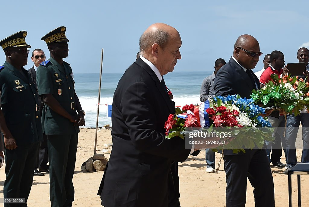 French Defence minister Jean-Yves Le Drian (C) and the representative of Ivory Coast's defence minister, Jean Paul Malan (R), prepare to lay wreaths of flowers in front of the Hotel Etoile du Sud on April 30, 2016 which was hit by a jihadist attack in March that left 19 people dead. France will increase the number of its troops in Ivory Coast, Defence Minister Jean-Yves Le Drian said on a trip to the African nation which hosts a regional base for French forces. / AFP / ISSOUF
