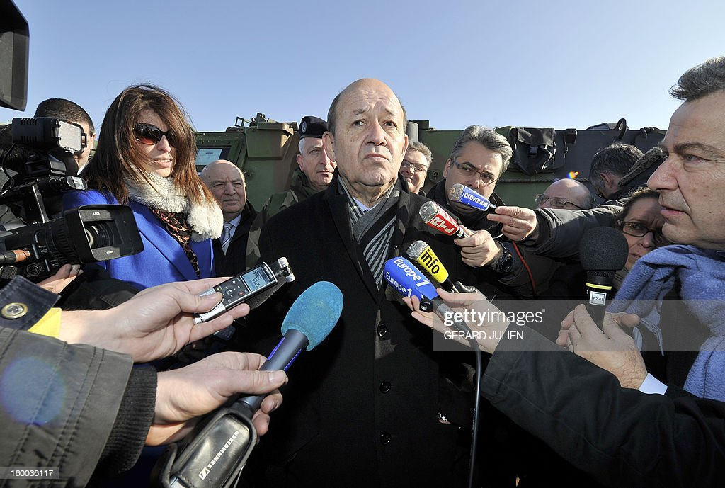 French Defence Minister Jean-Yves Le Drian (C) answers journalists questions as he pays a visit to French soldiers before their departure to Mali on January 25, 2013 at the Miramas ZRA (Zone de Regroupement et d'Attente) military base, southern France, as part of the French military operation codenamed Serval. Le Drian announced that 2400 French soldiers are now deployed in Mali as part of the operation Serval. AFP PHOTO / GERARD JULIEN