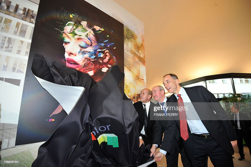 French Defence minister Jean-Yves Le Drian (C), Bretagne Regional Council president Pierrick Massiot (2R) and CEO of Technicolor Fred Rose unveal an image during the press conference inaugurating the new Technicolor research and development centre in Cesson-Sevigne near the central western city of Rennes on November 22, 2012. AFP PHOTO FRANK PERRY