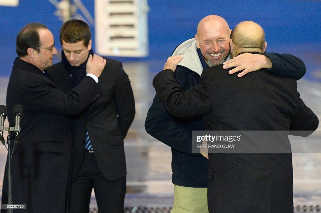 French Defence Minister Jean-Yves Le Drian (R) embraces Serge Lazarevic (2nd R), France's last remaining hostage, as French President Francois Hollande (2nd L) embraces Clement Verdon, the son of French executed hostage Philippe Verdon, after Lazarevic landed in a French Republic plane at the Villacoublay military base near Paris on December 10, 2014. Lazarevic, who was snatched by armed men in Mali on November 24, 2011, arrived home on December 10 after three years at the hands of Islamist militants, and was greeted by French President Francois Hollande. AFP PHOTO / BERTRAND GUAY