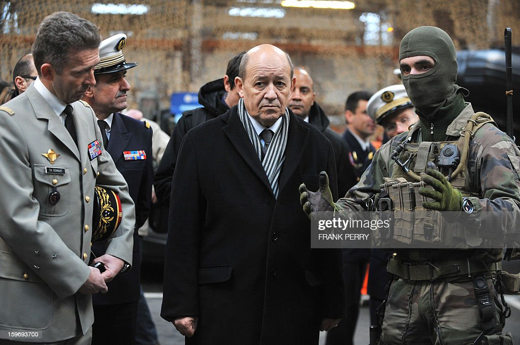 French Defence Minister Jean-Yves Le Drian (C), flanked by General Christophe Gomart (L), listens to explanations from a member of the French special forces (R) during his visit to a sniper commando base on January 18, 2013 in the northwestern French town of Lanester.