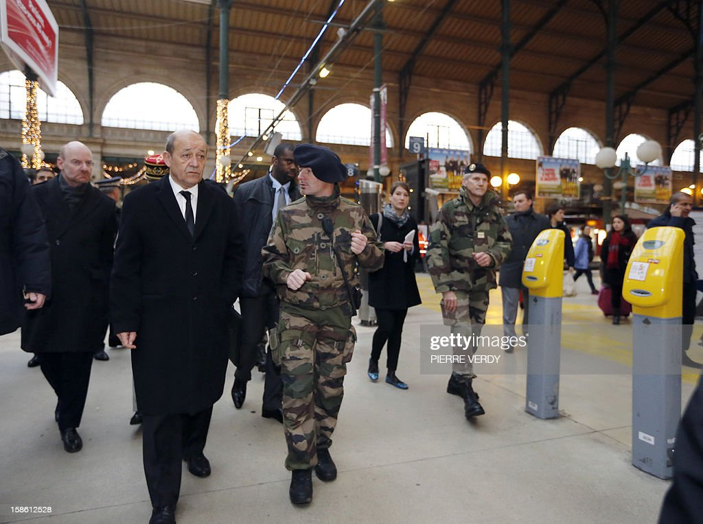 French Defence minister Jean-Yves Le Drian (C), flanked by General Secretary of French national rail company SNCF Stephane Volant (L), visits security forces deployed as part of France's national security alert system 'Plan Vigipirate' on December 21, 2012 at Gare du Nord railway station in Paris.