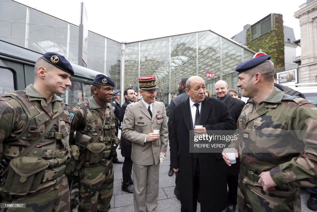 French Defence minister Jean-Yves Le Drian (C), flanked by Paris military governor, French army general Herve Charpentier, speaks with security forces deployed on December 21, 2012 at Gare du Nord railway station in Paris as France's national security alert system 'Plan Vigipirate' is reinforced for the Christmas holidays .