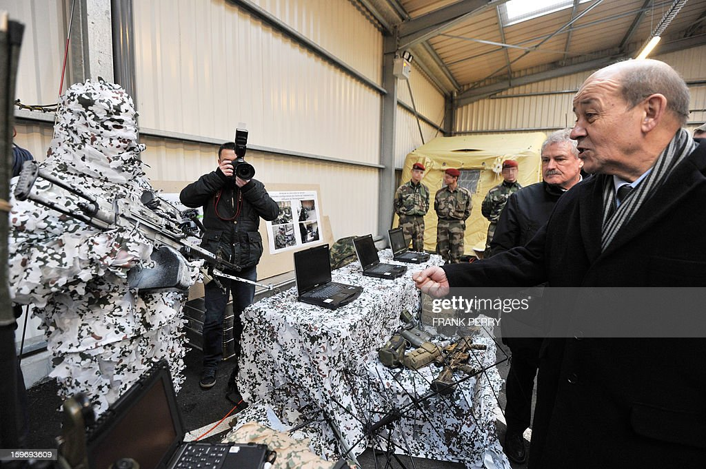 French Defence Minister Jean-Yves Le Drian (R) gestures in front of a camouflaged French special forces member (L) during his visit to a sniper commando base on January 18, 2013 in the northwestern French town of Lanester. AFP PHOTO / FRANK PERRY