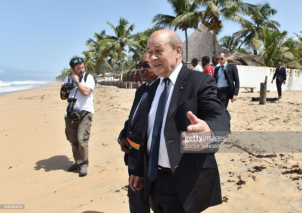 French Defence Minister Jean-Yves Le Drian (R) gestures next to Deputy Mayor of Grand-Bassam Guy Daniel Ouegnin, after laying wreaths in homage to the victims of a jihadist attack, on the beach of the Hotel l'Etoile du Sud in Grand Bassam on April 30, 2016. France will increase the number of its troops in Ivory Coast, Defence Minister Jean-Yves Le Drian said on a trip to the African nation which hosts a regional base for French forces. / AFP / ISSOUF