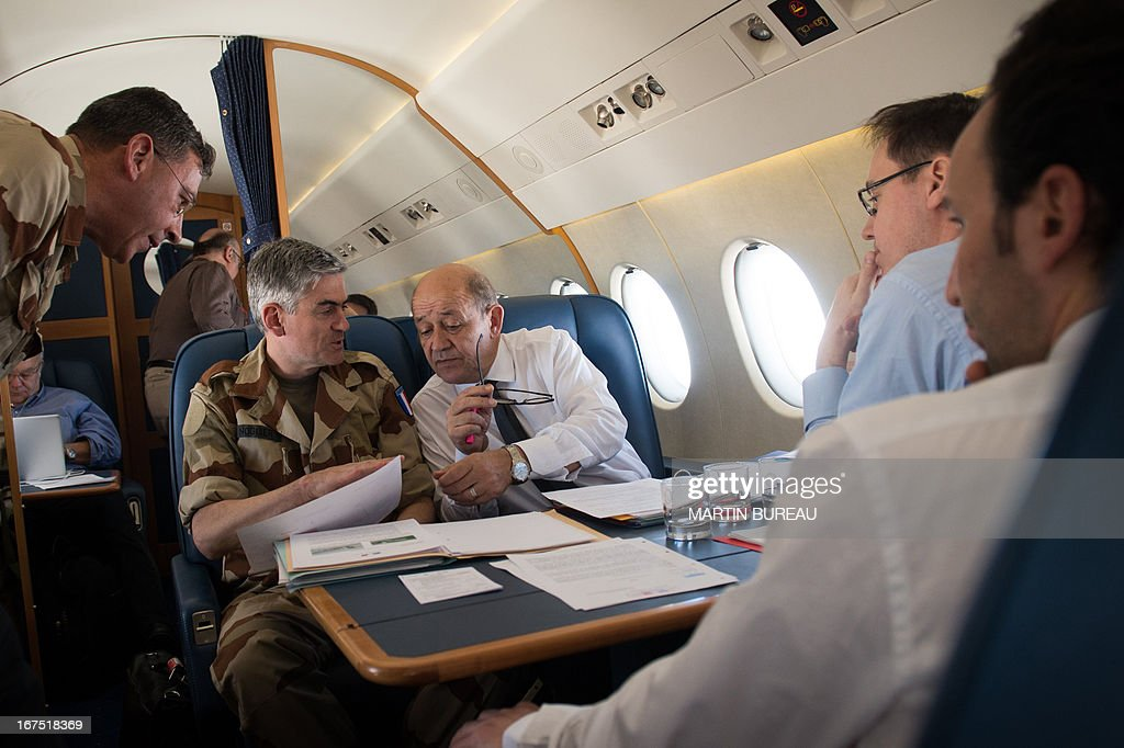 French Defence Minister Jean-Yves Le Drian (C) holds a breifing with his advisers aboard his plane en route to Mali on April 25, 2013. Le Drian arrived in the Malian capital on the first leg of a tour of several countries to prepare for a post-war Mali. Mali called on France's help in January to halt an Islamist advance on Bamako and French and African troops have since pushed the Al-Qaeda-linked militants into desert and mountain hideouts, from where they are staging guerrilla attacks. AFP PHOTO MARTIN BUREAU