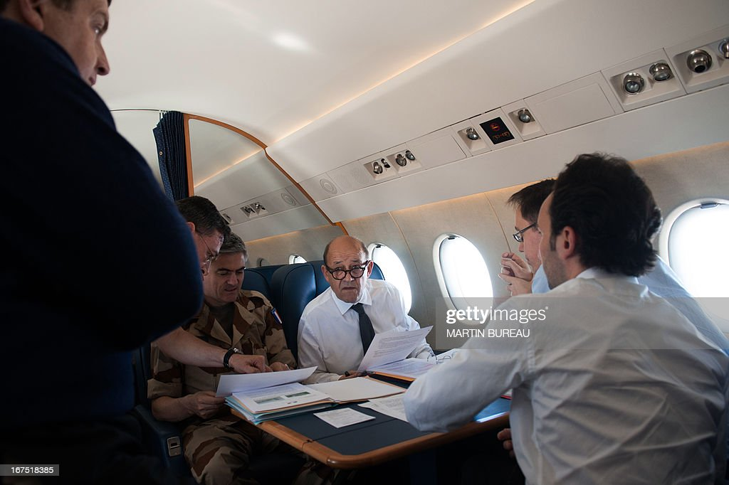 French Defence Minister Jean-Yves Le Drian (C) holds a breifing with his advisers aboard his plane en route to Mali on April 25, 2013. Le Drian arrived in the Malian capital on the first leg of a tour of several countries to prepare for a post-war Mali. Mali called on France's help in January to halt an Islamist advance on Bamako and French and African troops have since pushed the Al-Qaeda-linked militants into desert and mountain hideouts, from where they are staging guerrilla attacks.