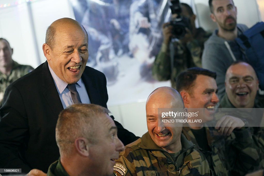 French Defence Minister Jean-Yves Le Drian laughs with French soldiers during the New Year's eve diner at Warehouse base in Kabul on December 31, 2012.