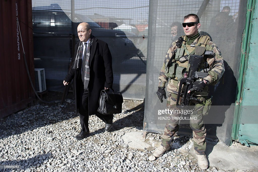 French Defence Minister Jean-Yves Le Drian (L) leaves the Warehouse base in Kabul on January 01, 2013.
