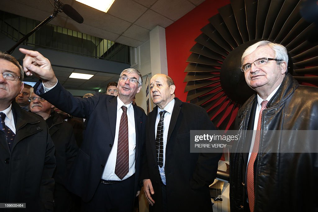 French Defence minister Jean-Yves le Drian (2ndR) listens to CEO of French aerospace and defence group Safran, Jean-Paul Herteman next to Marc Ventre (R), Safran Deputy Chief Executive Officer of Operations, on January 14, 2012 at the Safran / Snecma plant in Gennevilliers, near Paris.