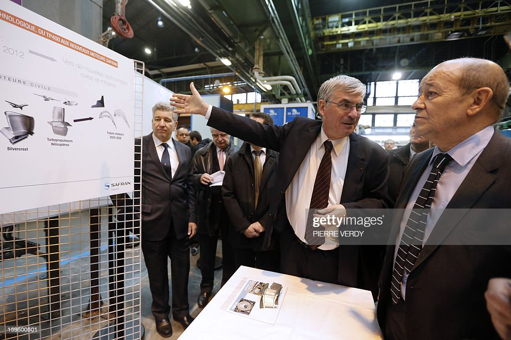 French Defence minister Jean-Yves le Drian (R) listens to CEO of French aerospace and defence group Safran, Jean-Paul Herteman during a visit, on January 14, 2012 at the Safran / Snecma plant in Gennevilliers, near Paris.
