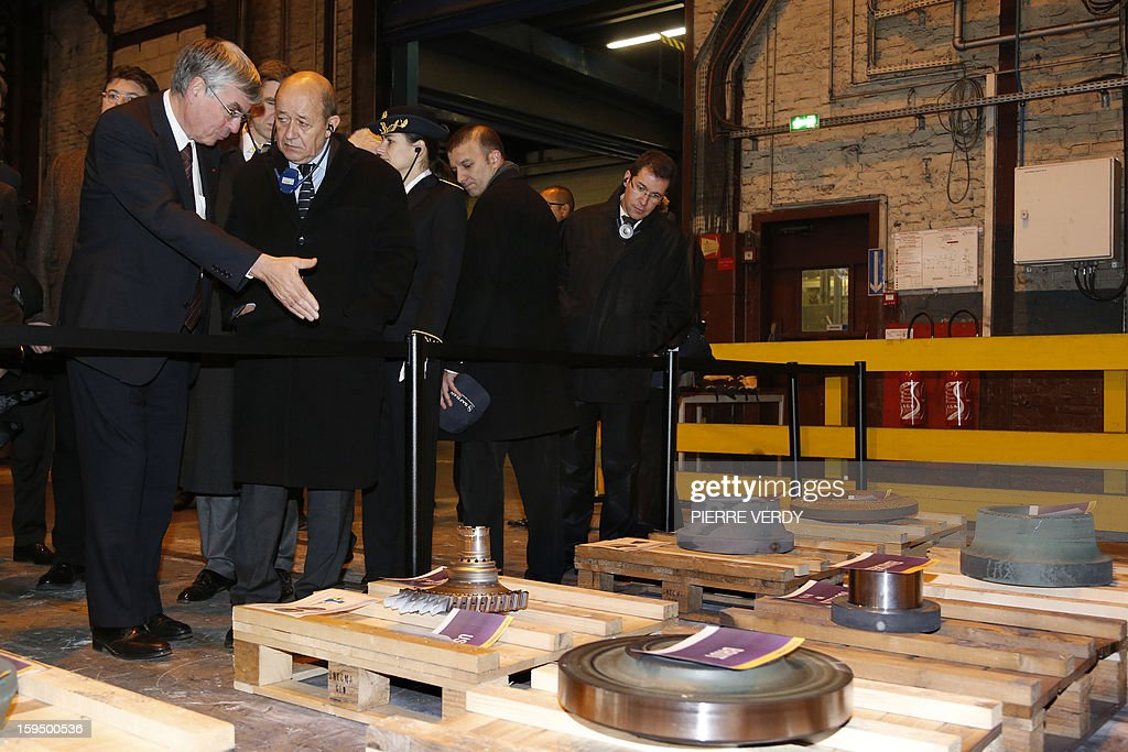 French Defence minister Jean-Yves le Drian (C) listens to CEO of French aerospace and defence group Safran, Jean-Paul Herteman during a visit, on January 14, 2012 at the Safran / Snecma plant in Gennevilliers, near Paris.