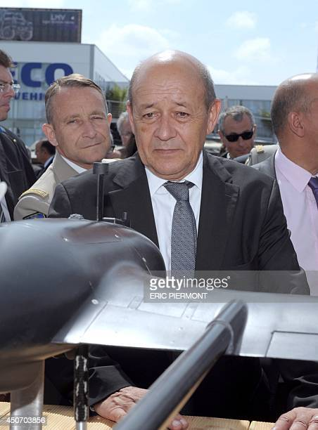 French Defence Minister JeanYves Le Drian listens to explanantions at the Airbus Group stand at the Eurosatory Exhibition in Villepinte near Paris on...
