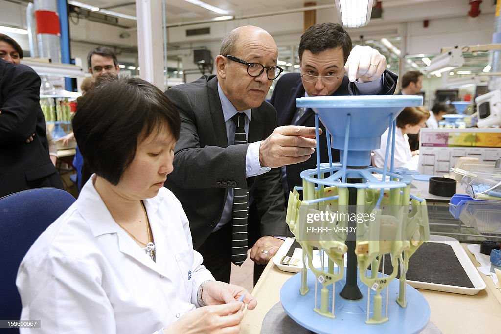 French Defence minister Jean-Yves le Drian (C) listens to explanations during a visit, on January 14, 2012 at the Safran / Snecma plant in Gennevilliers, near Paris. AFP PHOTO PIERRE VERDY