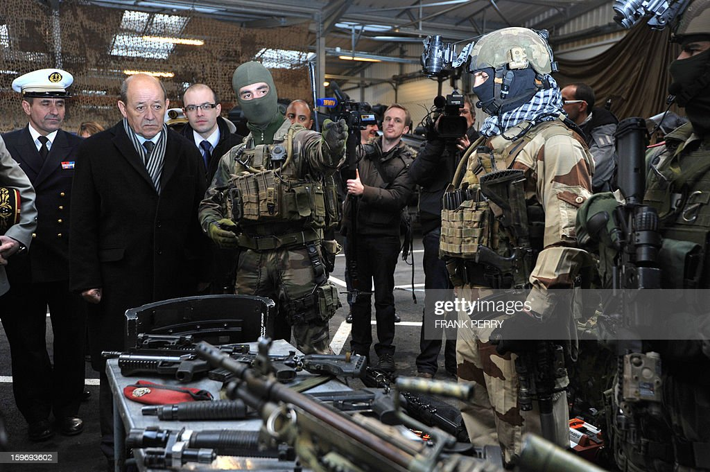 French Defence Minister Jean-Yves Le Drian (2ndL) listens to explanations from a member of the French special forces (C) during his visit to a sniper commando base on January 18, 2013 in the northwestern French town of Lanester. AFP PHOTO / FRANK PERRY