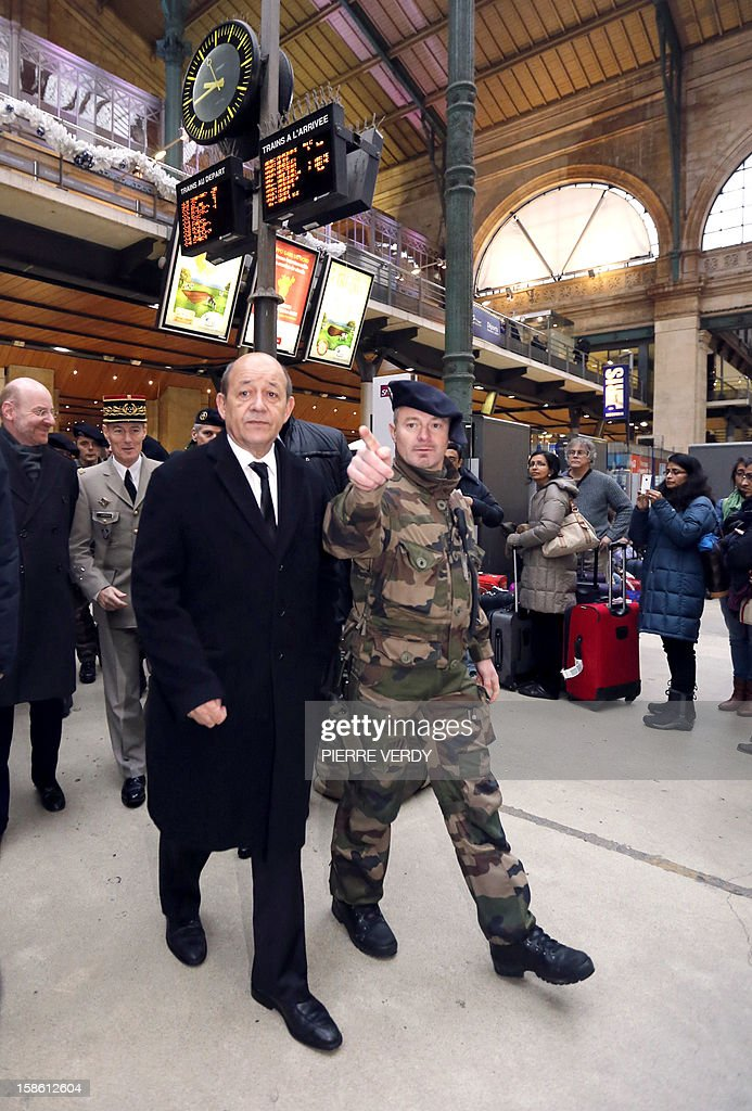 French Defence minister Jean-Yves Le Drian (foreground) listens to explanations as he visits with Paris Military Governor Herve Charpentier (2ndL) and General Secretary of French national rail company SNCF Stephane Volant (L) as part of a visit to security forces deployed as part of France's national security alert system 'Plan Vigipirate' on December 21, 2012 at Gare du Nord railway station in Paris.