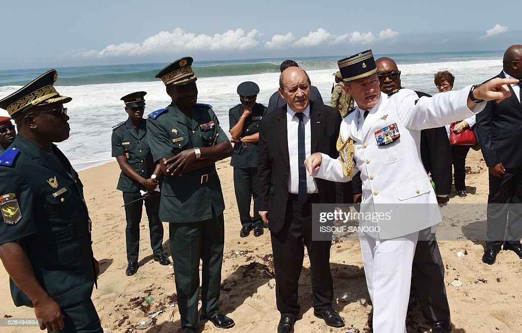 French Defence minister Jean-Yves Le Drian (C) listens to French and Ivory Coast army officers on the beach of the Hotel l'Etoile du Sud in Grand Bassam on April 30, 2016, which was hit by a jihadist attack in March that left 19 people dead. France will increase the number of its troops in Ivory Coast, Defence Minister Jean-Yves Le Drian said on a trip to the African nation which hosts a regional base for French forces. / AFP / ISSOUF