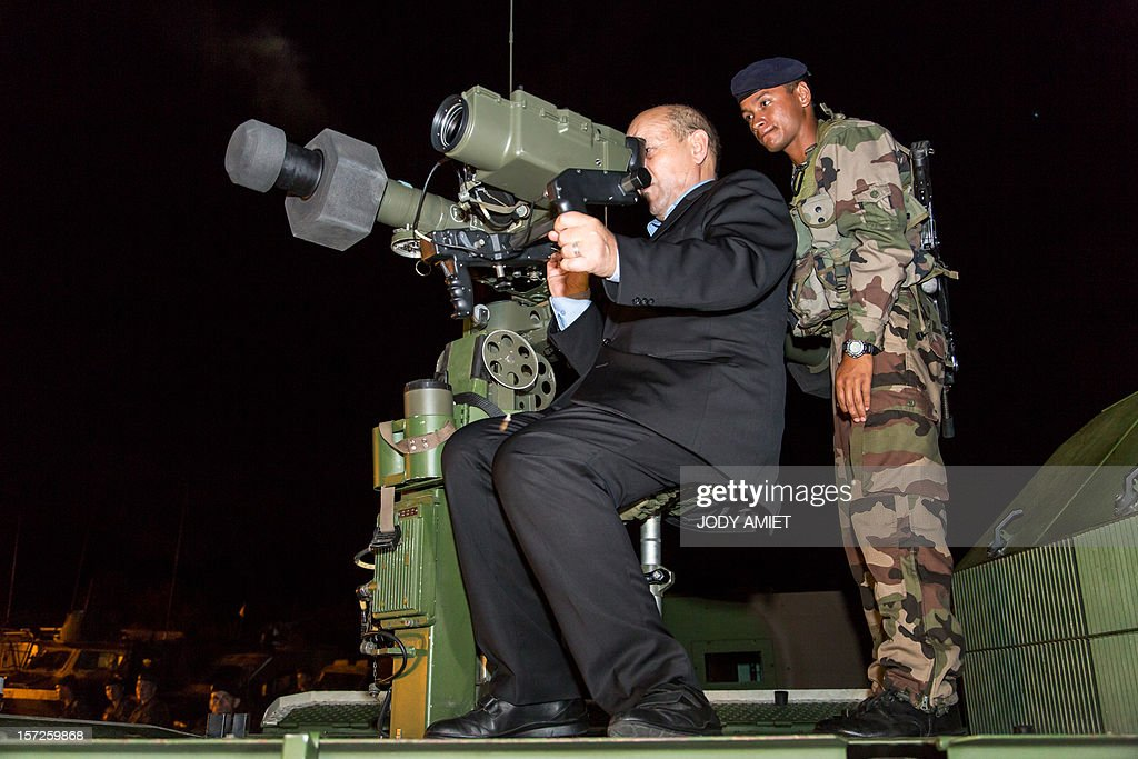 French Defence Minister Jean-Yves Le Drian (L) looks through the aiming system of a Mistral surface-to -air missile launcher as he meets legionnaires in charge of protecting the Titan mission at the Guiana Space Center in Kourou, French Guiana, on November 30, 2012, as part of a three-day visit.