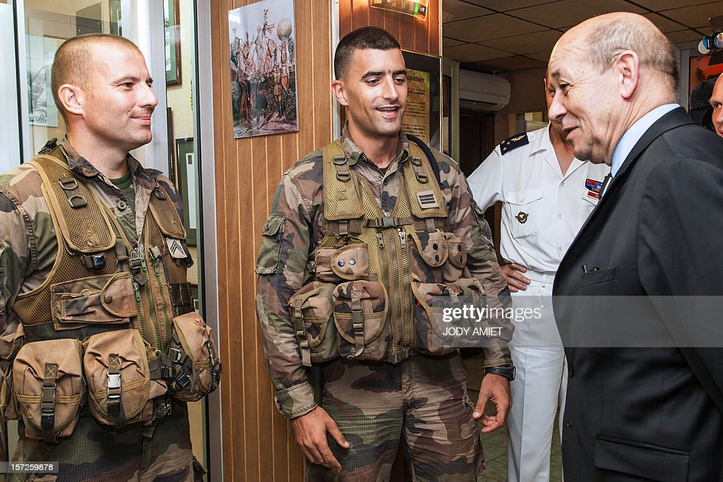 French Defence Minister Jean-Yves Le Drian (L) meets legionnaires in charge of protecting the Titan mission at the Guiana Space Center in Kourou, French Guiana, on November 30, 2012, as part of a three-day visit.